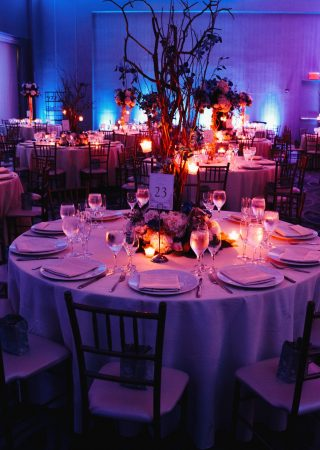 Decorated wedding hall with candles, round tables and centerpieces